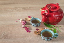 Tea Time Concept. Red Teapot, Two Chinese Cup Of Tea, Rose Buds On Wooden Background. Close Up, Selective Focus