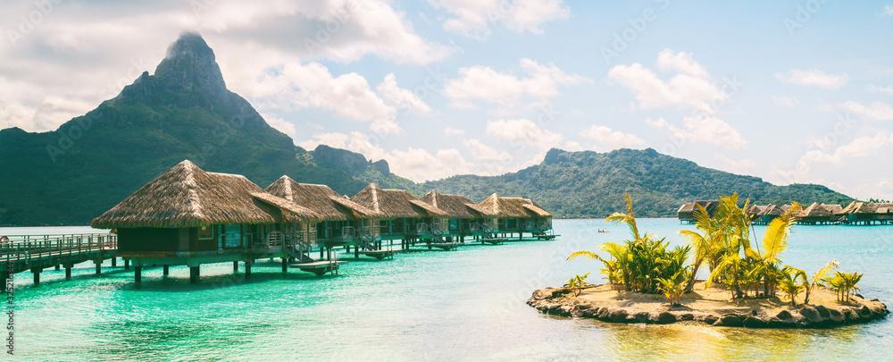 Fototapeta Bora Bora French Polynesia luxury hotel resort overwater bungalow suites in Tahiti, Honeymoon travel destination header panorama background.