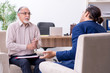 Young man visiting old male doctor psychologist