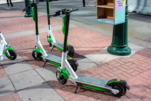 Scooter Rental Service On Sidewalk In Downtown - Sharing Economy