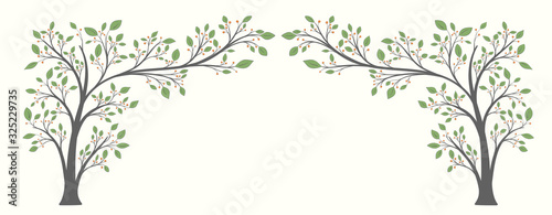 Photo Two flowering trees with leaves and berries in the form of an arch on a light ba
