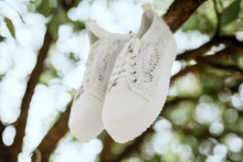 White Wedding Sneakers Hanging On A Tree Branch. Focused On The Front Of The Sneaker. In The Background Blurred Branches And Leaves Of Trees With A Shining Arc In The Form Of Defocused Bokeh.