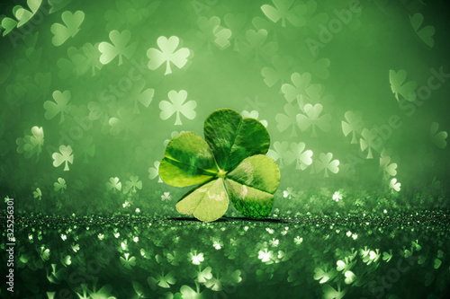 Fotografia Lucky four leaf clover surrounded by sparkling shamrock shapes