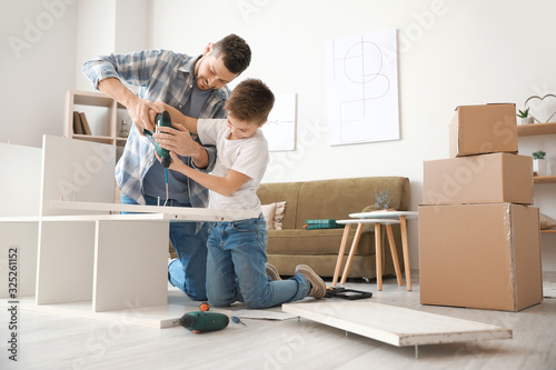 Fototapeta Father and his little son assembling furniture at home