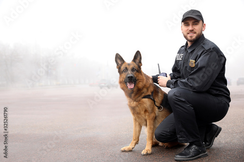 Male police officer with dog patrolling city street Fotobehang