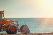 Yellow Bulldozer Rides On The Beach. In The Background Sea And Sky. Light From The Right Side. Copy Space