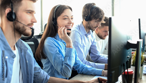 Portrait of call center worker accompanied by her team Canvas Print
