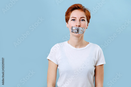 Portrait of an emotionless woman with short ginger hair and mouth taped Fototapet