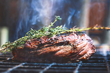 Juicy Grilled Beef Tenderloin, Cooked Steak Meat, Food. Barbecue With Smoke Filet Mignon. The Meat Is Cooked, Fried Over A Fire With Dark And Rosemary. Provencal Herbs. Close-up, Macro.