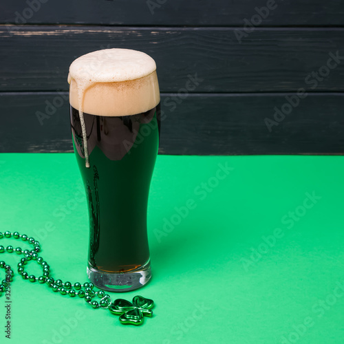Canvas Print Glass of dark stout beer and traditional clover shaped decor on green table
