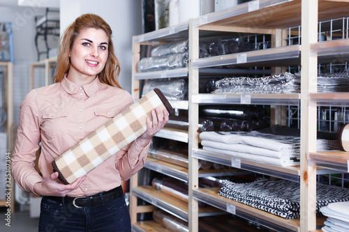 Photo Adult salesgirl suggesting carpet for bathroom