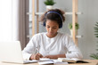 Focused african african teen girl wearing headphones writing notes studying