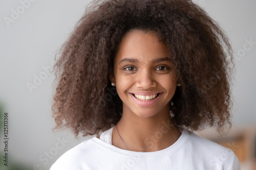 Fényképezés Headshot of smiling cute teenage african girl looking at camera