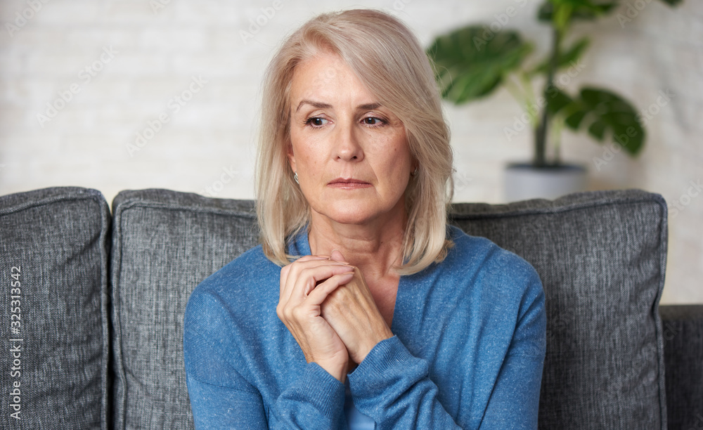 Fototapeta Sad senior woman is sitting on a sofa at home