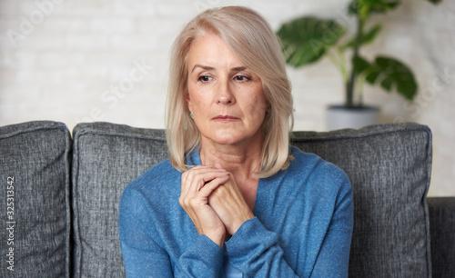 Photo Sad senior woman is sitting on a sofa at home