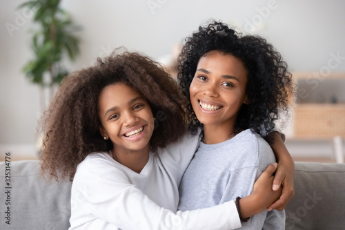 Fotomural Happy african mother and teen daughter embracing looking at camera