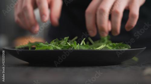 Photo man hands arranging fresh arugula on black plate
