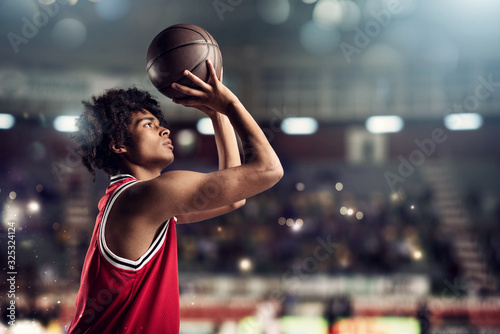 Basketball player throws the ball in the basket in the stadium full of spectator Fotobehang