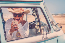Happy Adult Beautiful Young Woman Inside An Old Vintage Trendy Blue Van Enjoying The Trip And Travel Lifestyle Looking With Surprise Her Mobile Phone With Internet Connection - Alternative People