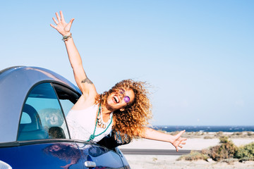 Happy and joyful people in outdoor travel leisure activity - beautiful curly blonde woman have fun outside the window of a blue vehicle car - concept of transport and happiness - ocean background