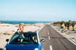 canvas print picture - Travel friends and transport with blue convertible car and couple of adult women friends have fun together driving on a long road with ocean in background - youth female stand up outside the roof
