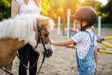 Cute little girl and her older sister enjoying with pony horse outdoors at ranch..