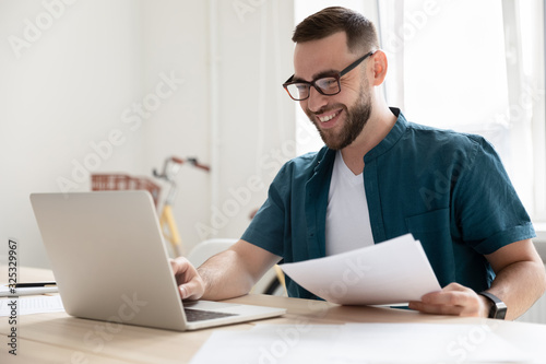 Obraz Happy young businessman in eyeglasses working on computer. - fototapety do salonu