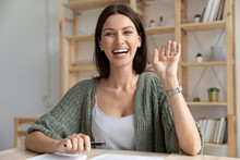 Happy Young 30s Woman Waving Hello To Camera.