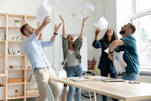 Overjoyed Young Multiracial Business Team Throwing Paper Documents In Air.
