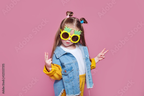 Obraz Summer fashion concept. cheerful little girl in big pineapple sunglasses on pink background - fototapety do salonu