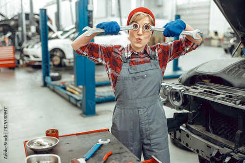Caucasian girl holding a pair of spanners