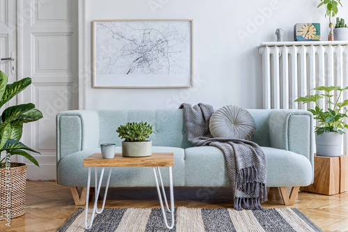Fototapeta Stylish scandinavian living room interior with design mint sofa, furnitures, mock up poster map, plants, and elegant personal accessories. Modern home decor. Bright and sunny space. Template.  obraz na płótnie