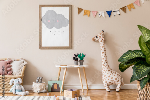Stylish and beige scandinavian interior of kid room with mock up poster frame, design furnitures, natural toys, hanging colorful flags, plush animal, child accessories and teddy bears. Home decor.