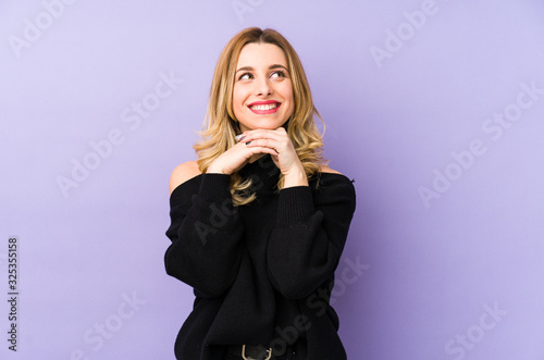 Young blonde woman isolated keeps hands under chin, is looking happily aside Fototapet