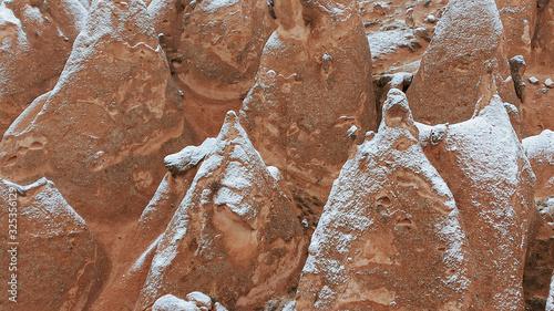 Fairy chimneys with snowy landscape at Devrent Valley in Cappadocia. Unique rock formations in Imaginary Valley in winter season in Cappadocia.