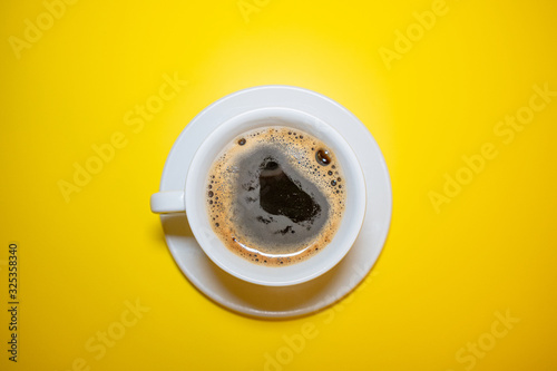Foto White coffee Cup with foam saucer on a bright yellow background top view, minima