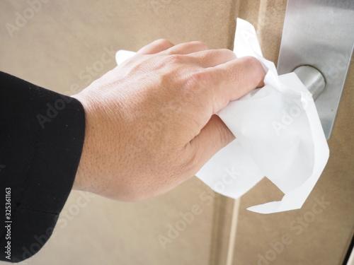 Photo 指先へのウイルス付着防止のためティッシュペーパーで指を保護してからドアノブを握る人