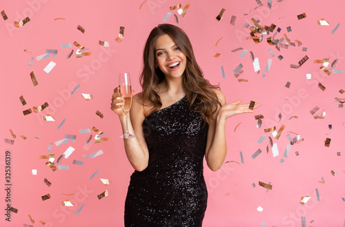 Glamour Woman Standing With Glass Of Champagne Under Falling Confetti - 325361319