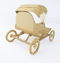 Back View Of A Brown Colored Carriage Made Of Recycled Card-board Displayed On A White Background