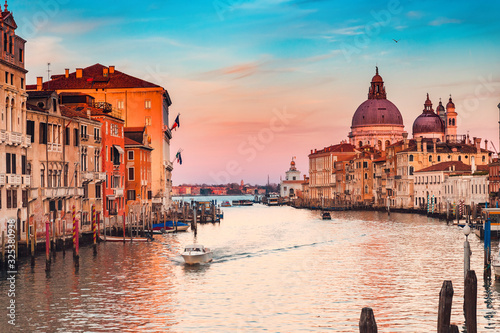 Fototapeta Gondolier carries tourists on gondola sunset Grand Canal of Venice, Italy obraz
