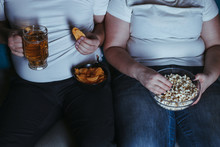 Relationship Problems, Emotional Eating, Laziness. Overweight Couple Watching Tv Eating Junk Food