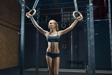 Female Crossfit Athlete In Black Sportswear Holding Dip Rings Relaxed And Looking Away, Arms Apart Fitness Girl Exercising With Gymnastic Rings In Gym. Fit Young Woman Training Gymnastics Rings In Gym