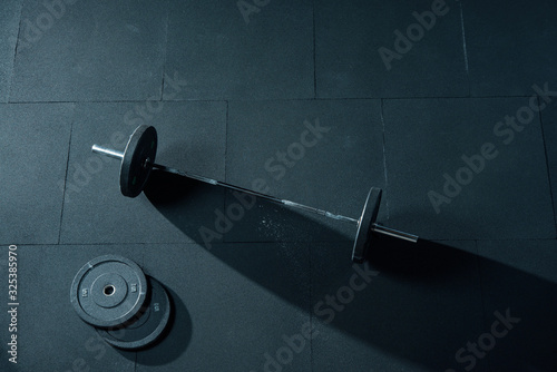 Obraz Fitness equipment for workout in Gym. Barbell with two weights plates on floor. Weight Olympic Bar Mockup Template Horizontal photo. Bright side light, sharp shadow. Top view - fototapety do salonu