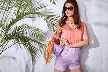 Glamour Fashion Lady Stylish Clothes Model Pose Woman With Dark Hair Wear Red Silk Blouse  Short Jewelry Or Bijou Sunglasses Accessory Style Bag Sun Shadow Green Palm Leaves Tan Body Skin Shape.