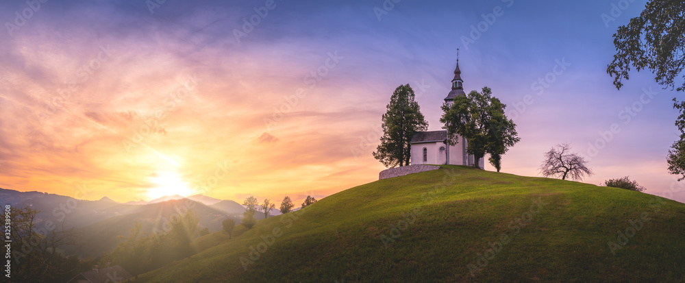 Fototapeta Astonishing colorful summer sunset in Slovenian Alp mountains with St Tomaz church. Travel destination Slovenia