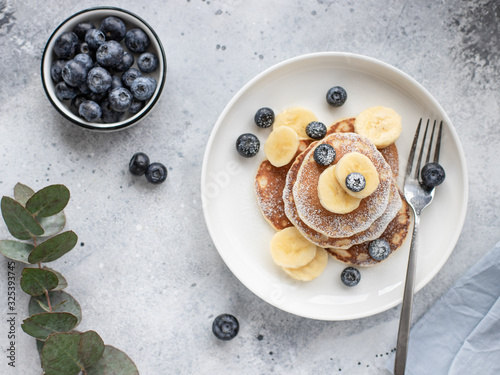 Leinwand Poster pancakes with fresh blueberries, banana in a white plate on a gray background with a branch of eucalyptus