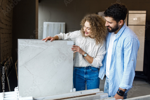 Happy young couple pointing at ceramic tile for bathroom floor in store Canvas Print