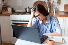 Upset Woman Working From Home Office. Unhappy Freelancer Using Laptop And The Internet. Workplace In Cozy Kitchen. Concept Of Female Business And Career, Housekeeping, Stress. Lifestyle Moment.