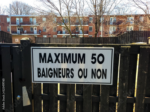 Sign on a Fence That Says Maximum 50 Baigneurs ou Non (50 Swimmers Maximum or No Canvas Print