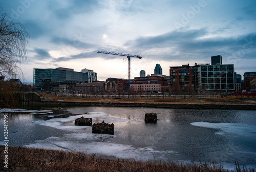 Photo Lachine Canal with Ice Parts and Small Wooden Structures with Buildings and a Co